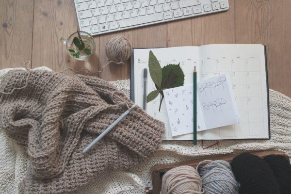 tricot en cours posé sur bureau avec cahier et clavier
