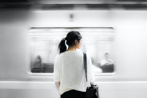 une femme devant un métro qui passe